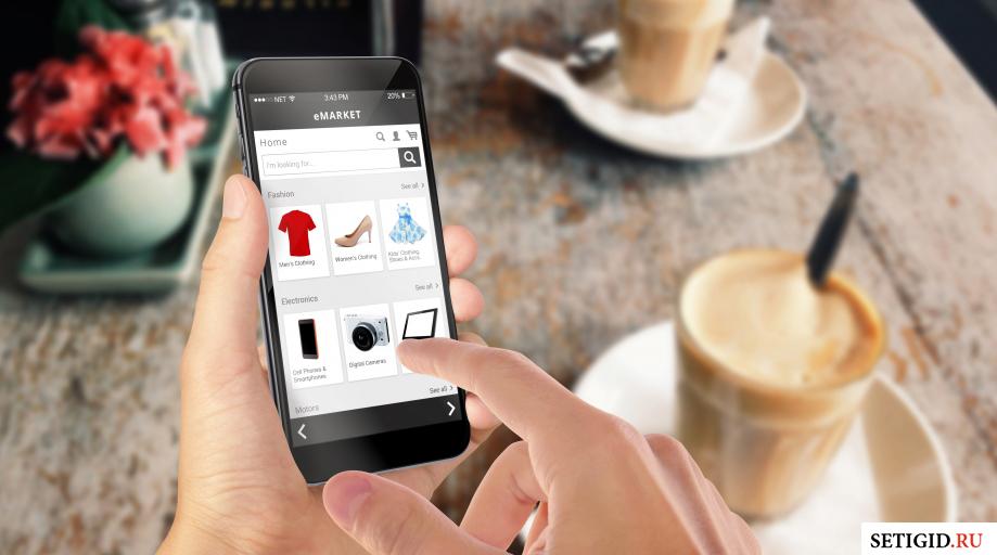 Смартфон в руках на фоне чашки кофе и стола