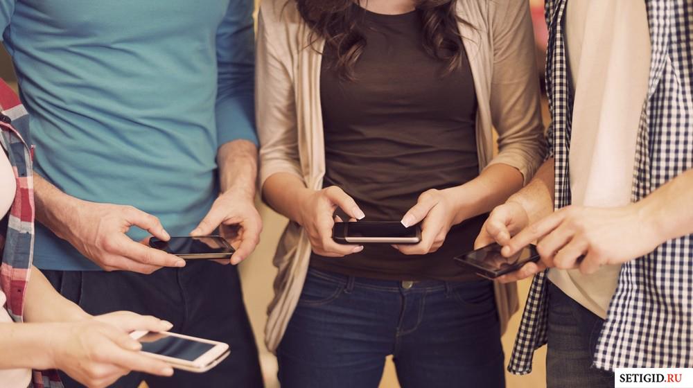 группа людей со смартфонами в руках