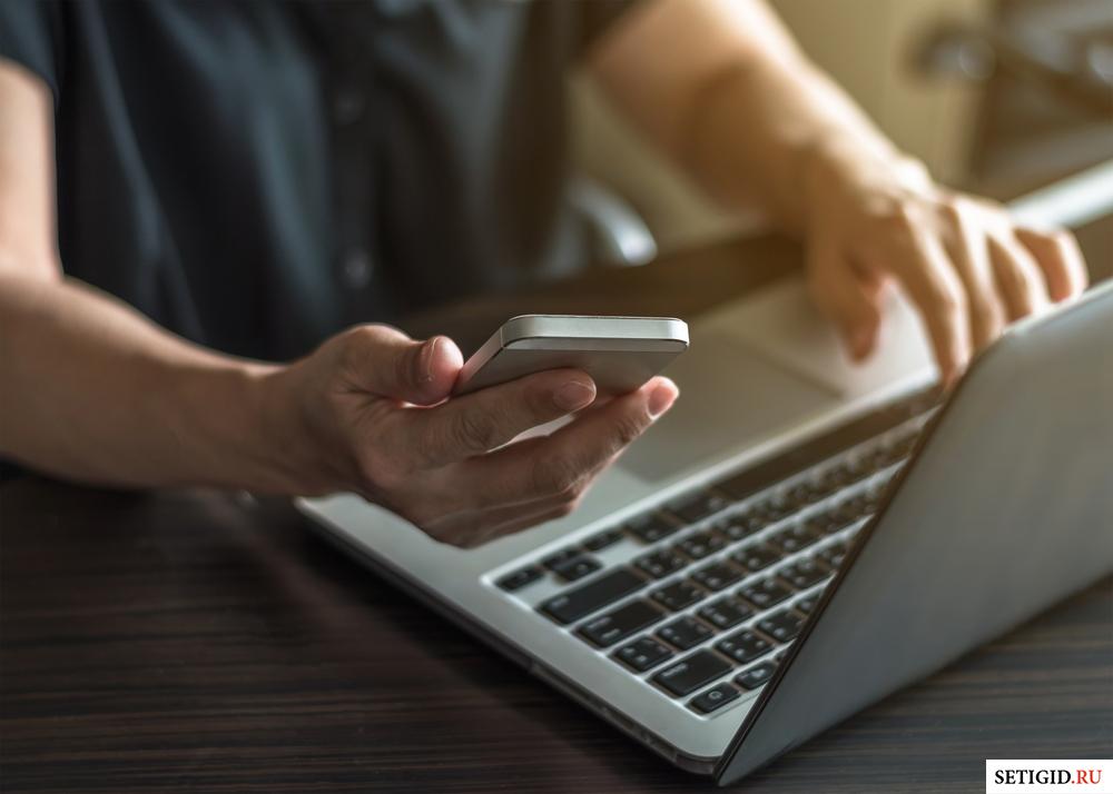 Человек за столом с ноутбуком и телефоном в руках
