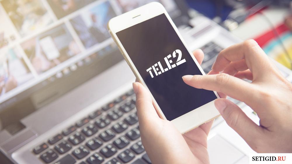 телефон в руках с надписью теле2 на экране