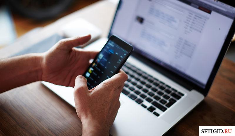 Мобильный телефон в руках перед макбуком