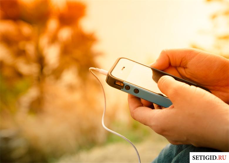телефон в руках на оранжевом фоне