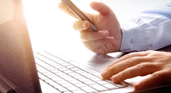 набор текста на клавиатуре ноутбука с телофоном в руках