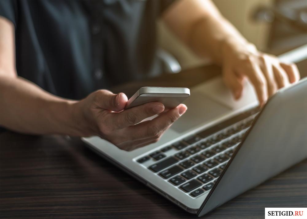 человек держит в руках теелефон и ноутбук на столе