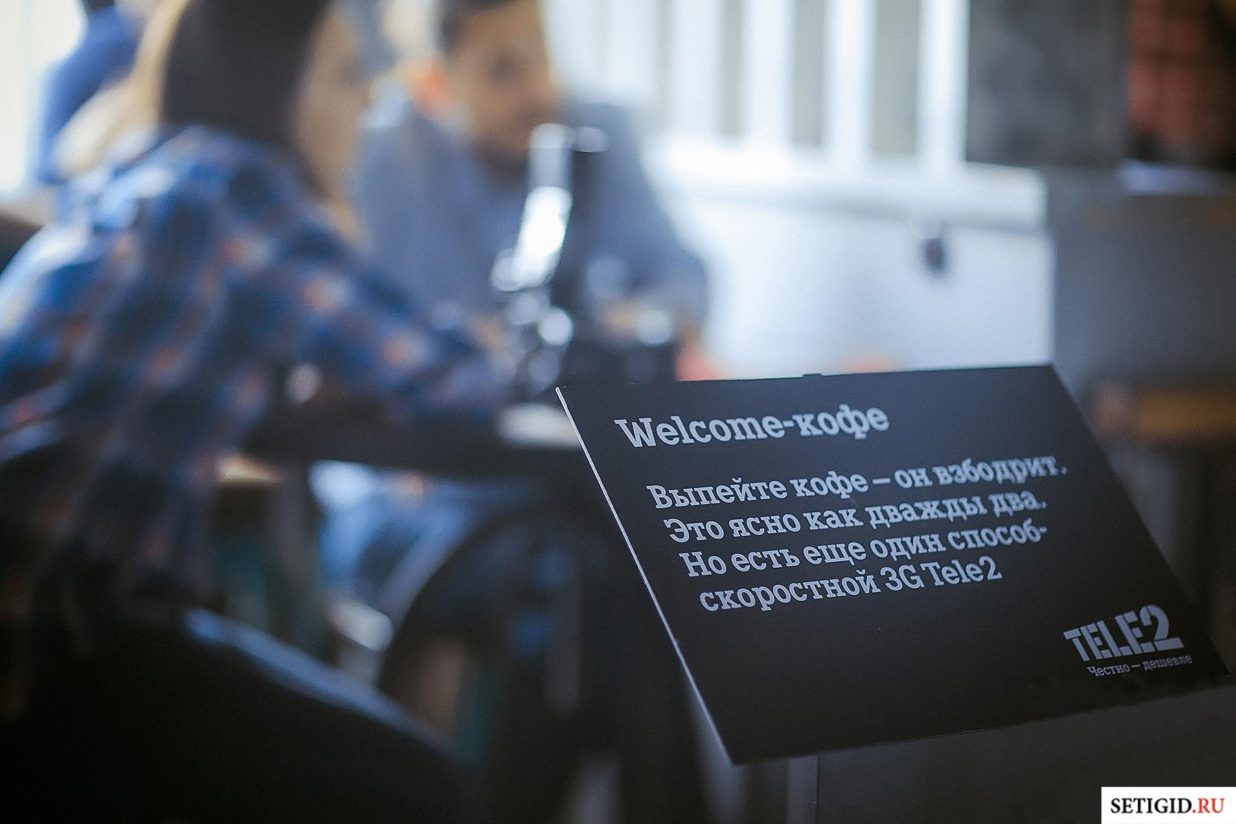 рекламная карта теле 2 в руках на фоне офиса