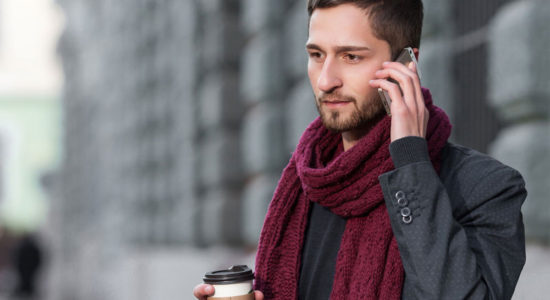 рчеловек гвоорит по телефону на фоне города