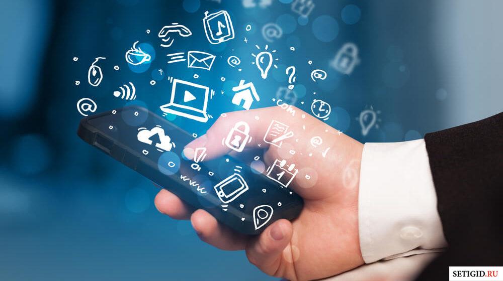 Человек держит телефон в руке с медиа иконками в воздухе