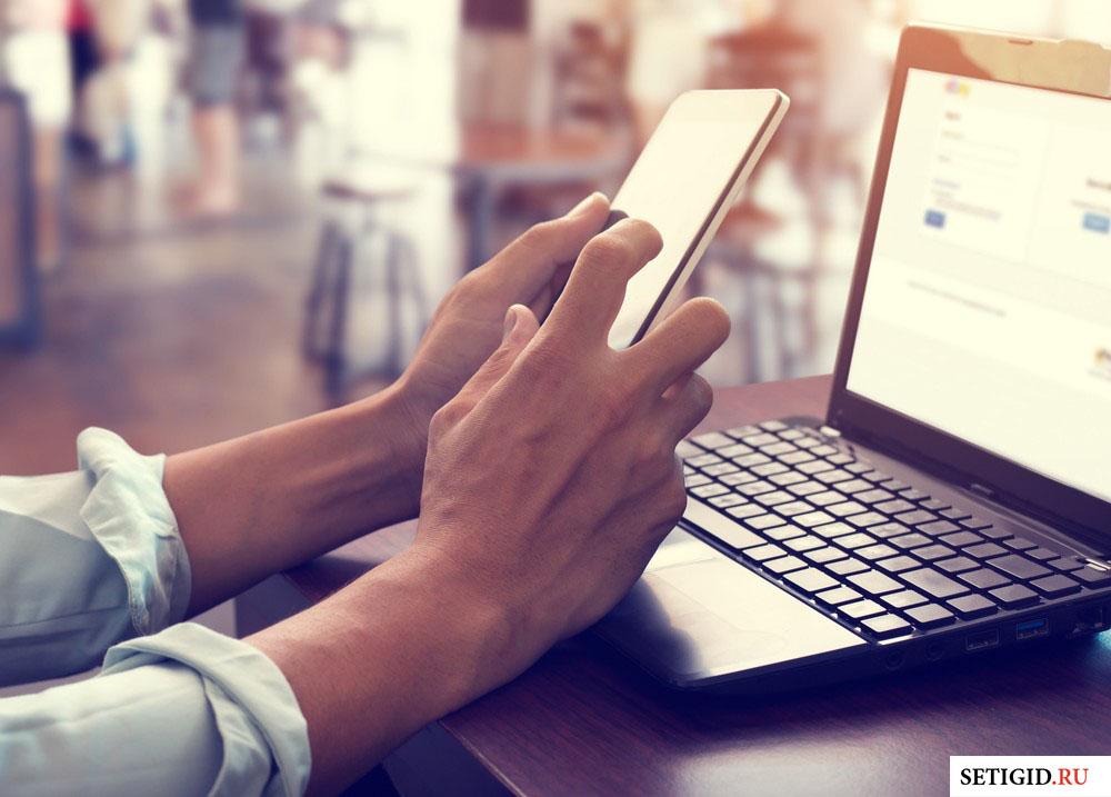 телефон в руках перед ноутбуком