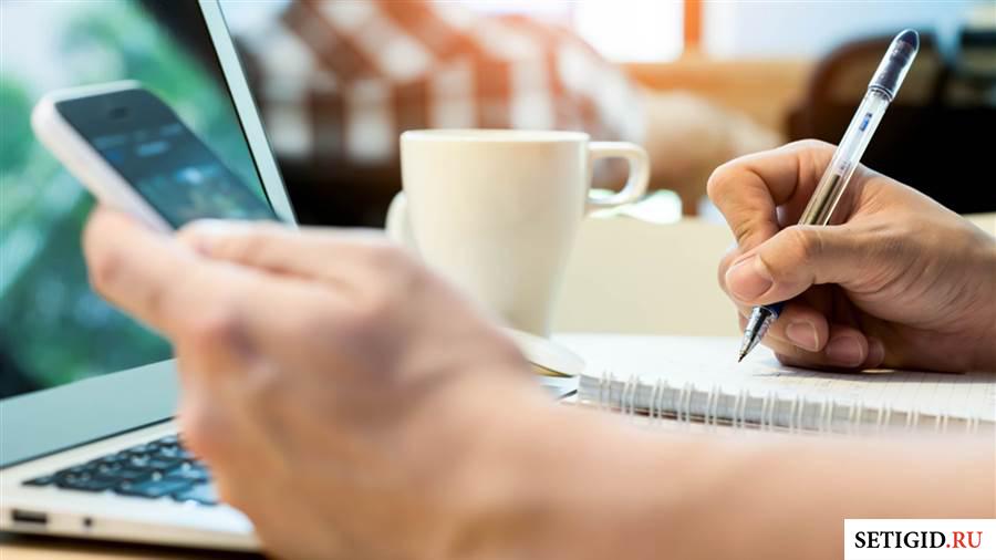 Мобильный телефон в руках и ручка перед ноутбуком