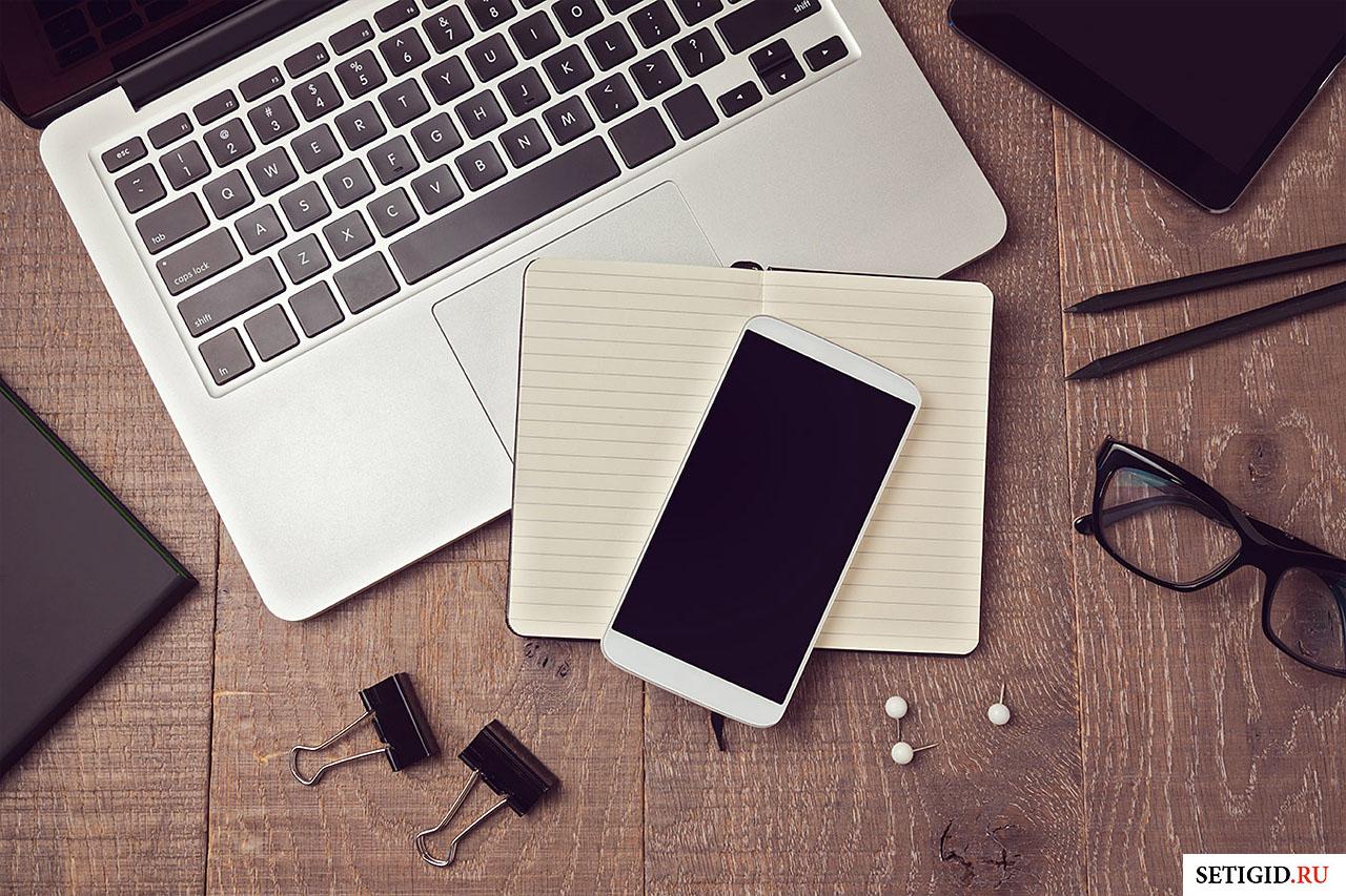 Ноутбук и телефон на рабочем столе