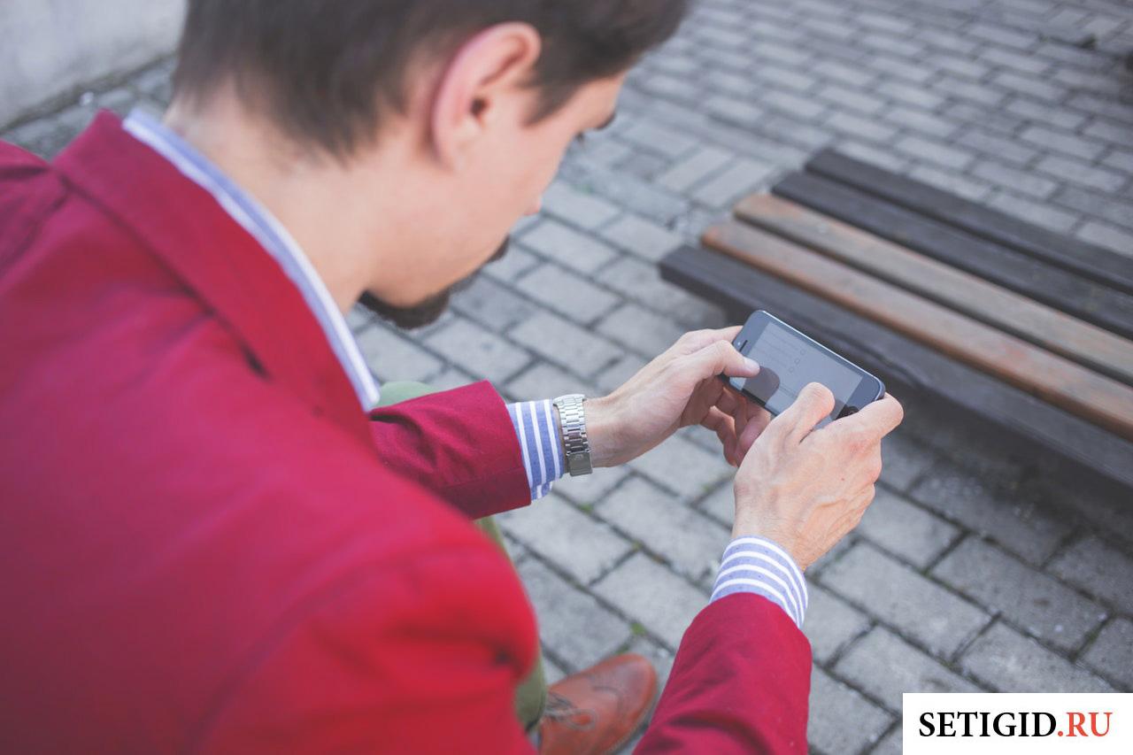 парень держит в руках мобильный