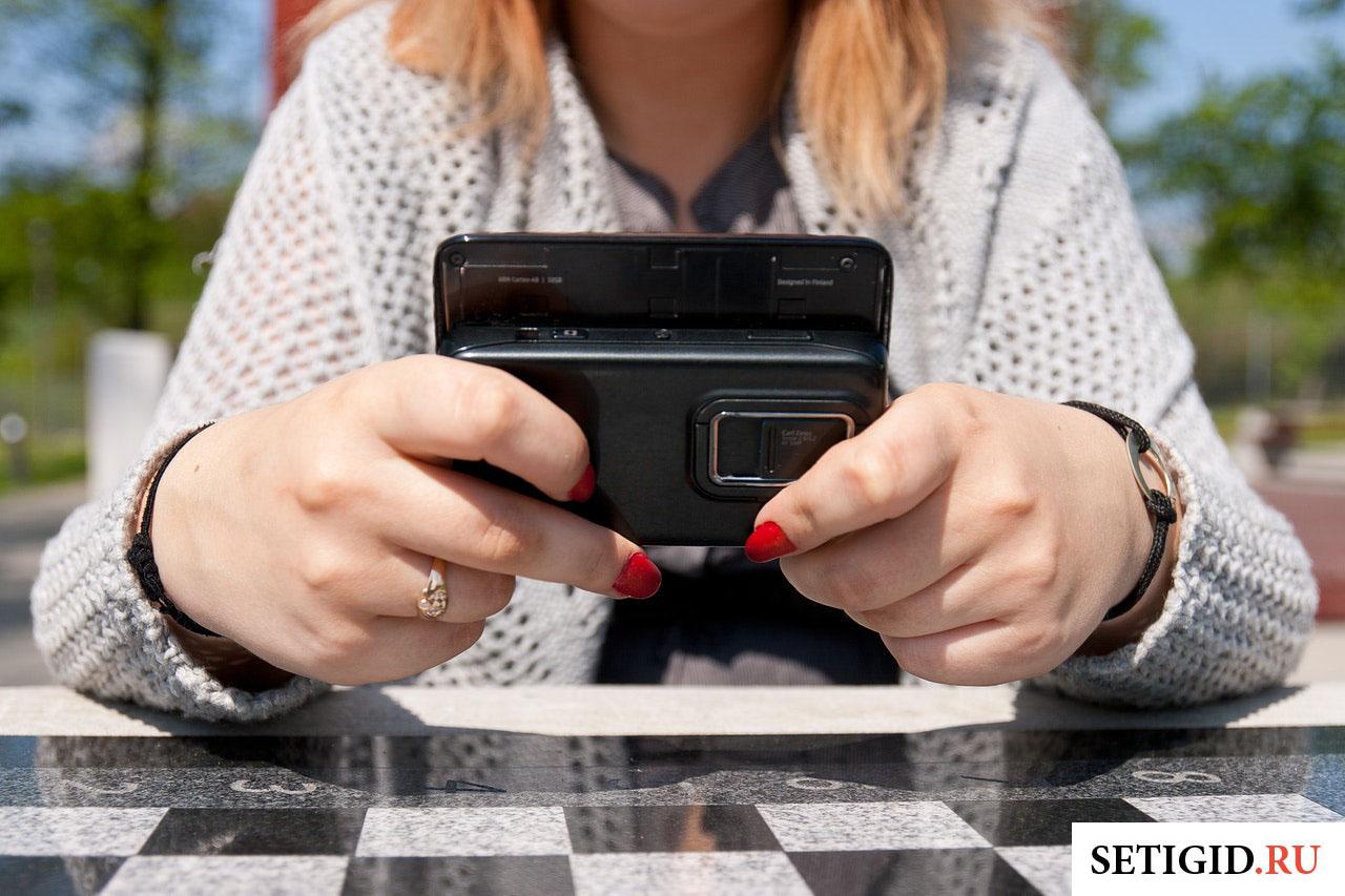 девушка держит в руках телефон