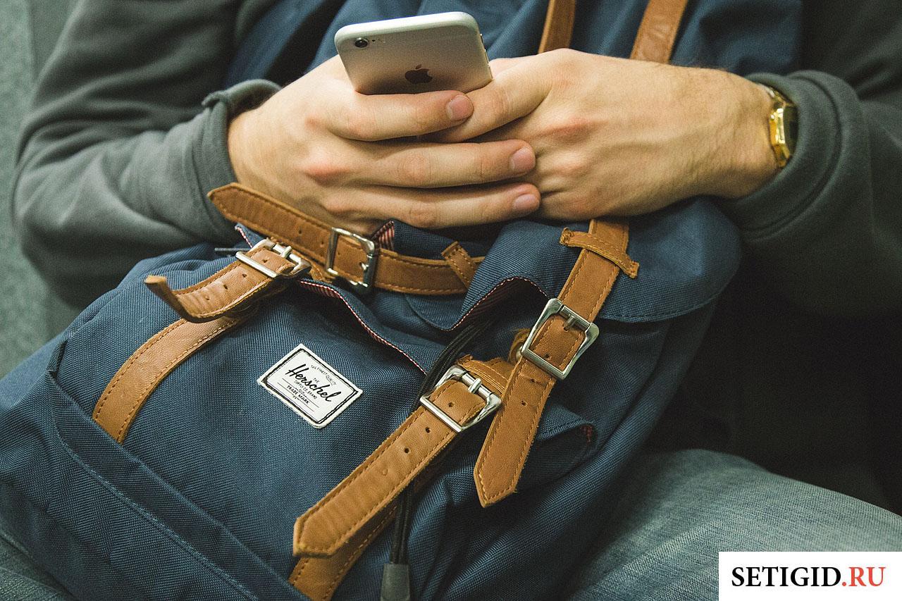 мобильный телефон в руках туристический рюкзак