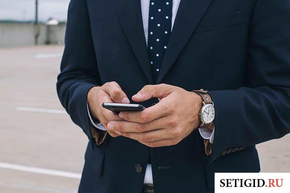 бизнесмен держит в руках мобильный телефон