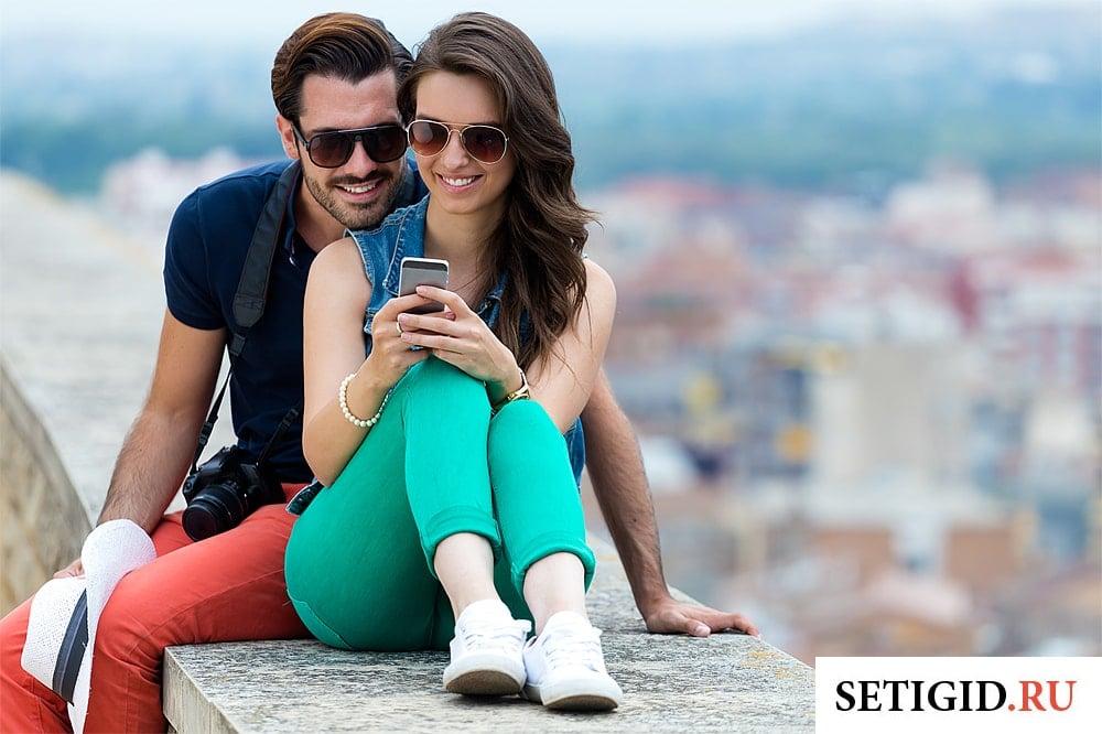 парень и девушка смотрят на экран мобильного телефона