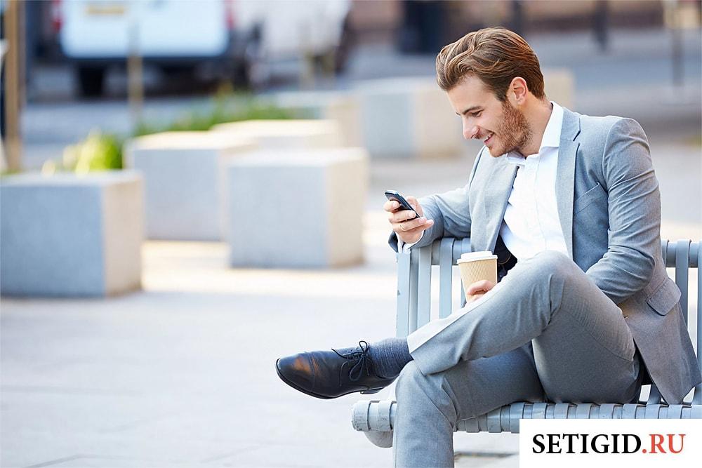 человек в деловом костюме с телефоном в руках