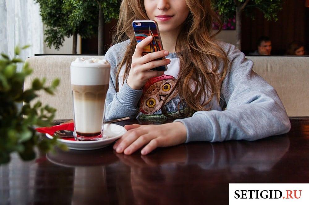 девушка сидит в кафе и держит в руках смартфон