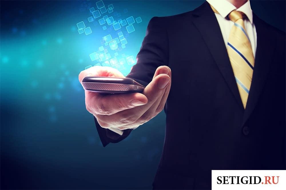 мужчина в деловом костюме держит в руке телефон