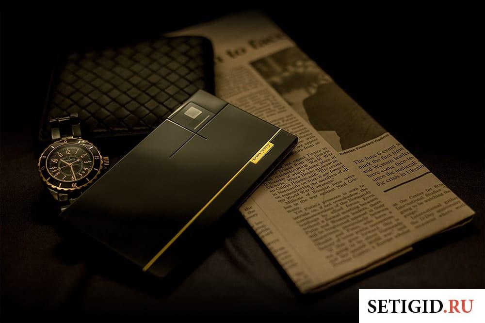 смартфон лежит рядом с часами портмоне и газетой