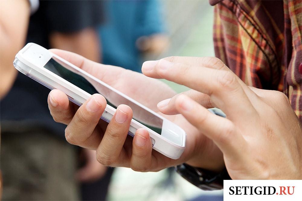 белый мобильный телефон в руках