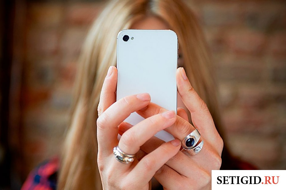 девушка держит перед собой телефон