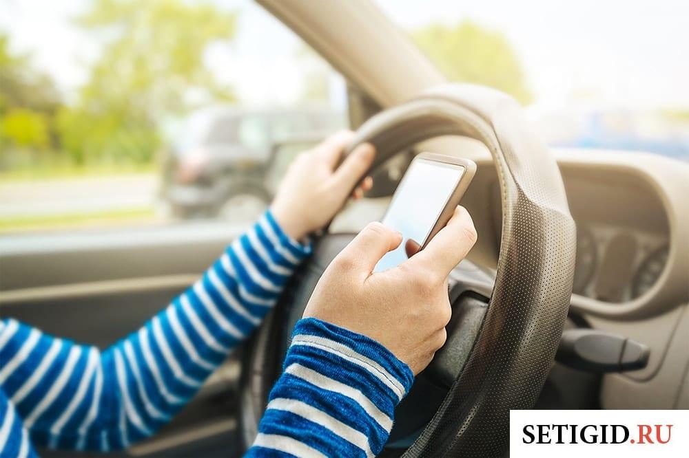 женщина водитель с телефоном в руке