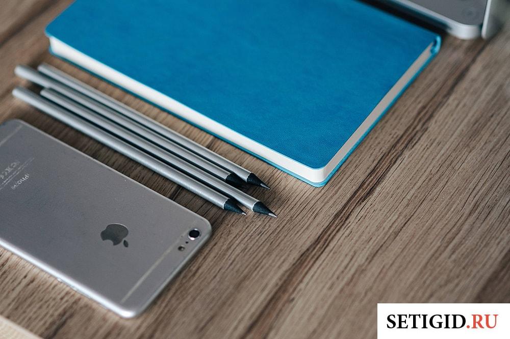 айфон ручки и блокнот лежат на столе