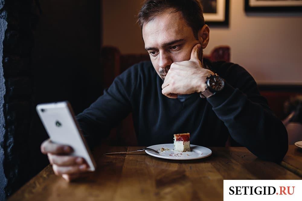 мужчина сидит в кафе за столиком и держит в руке смартфон