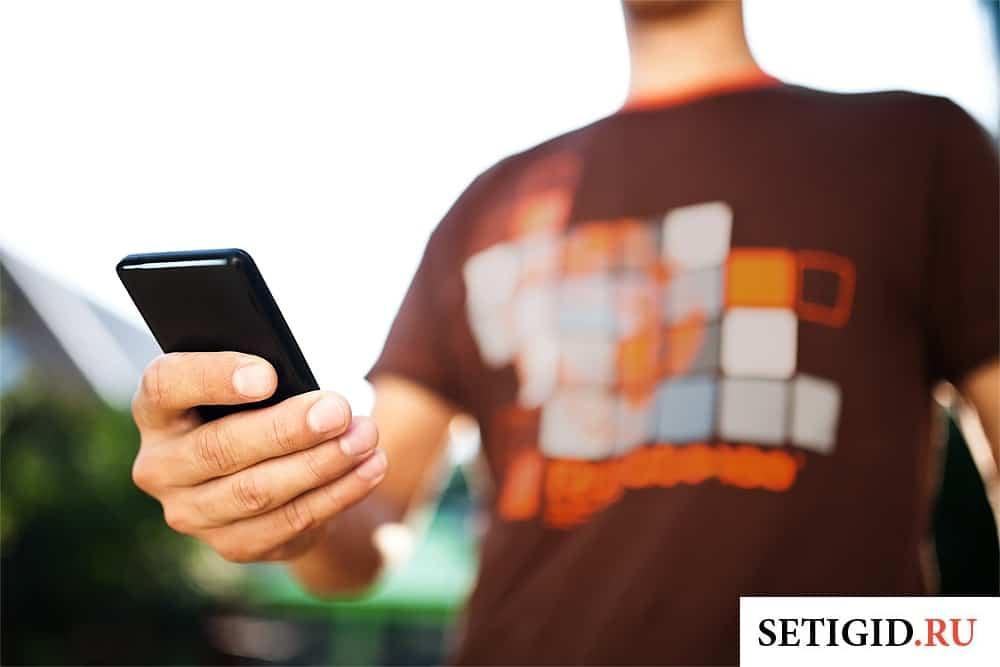 парень держит в руках смартфон