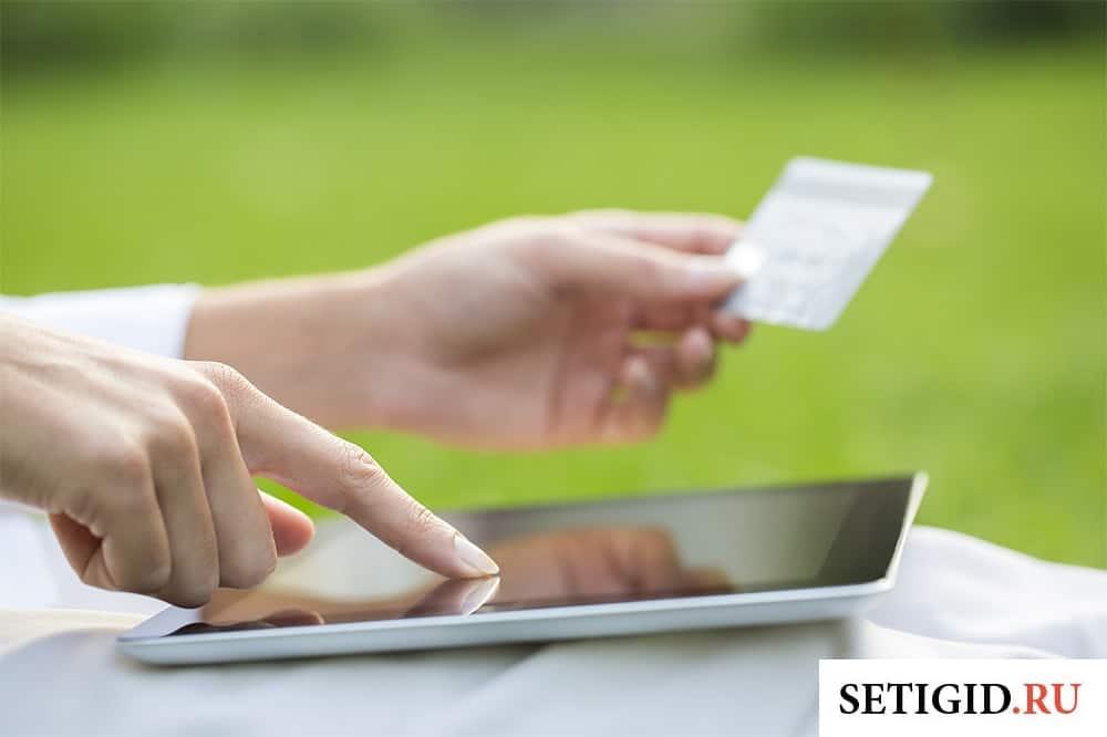 планшет и банковская карта в руках