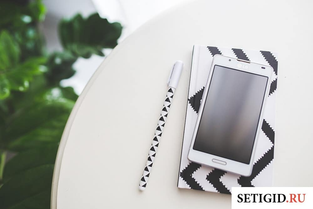 мобильный телефон блокнот ручка лежат на столе