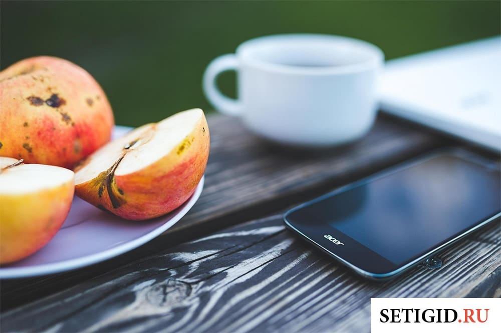 мобильный телефон и тарелка с яблоками на деревянном столе
