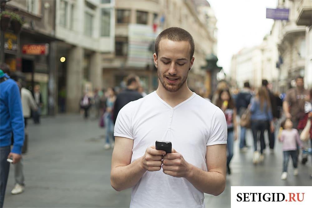 молодой человек с телефоном в руках идет по улице
