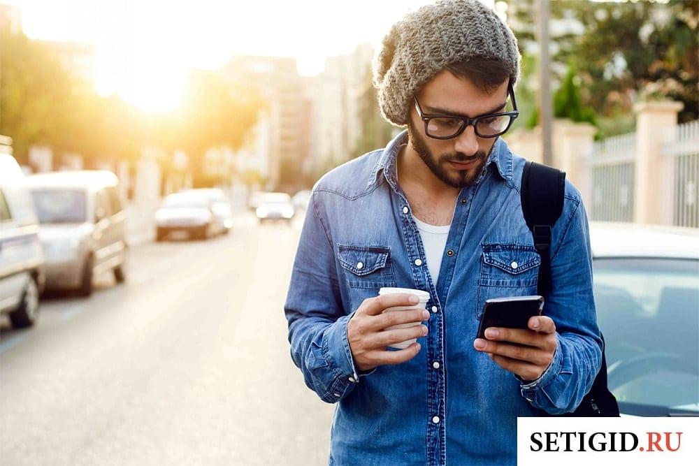 молодой человек с мобильным телефоном идет по дороге