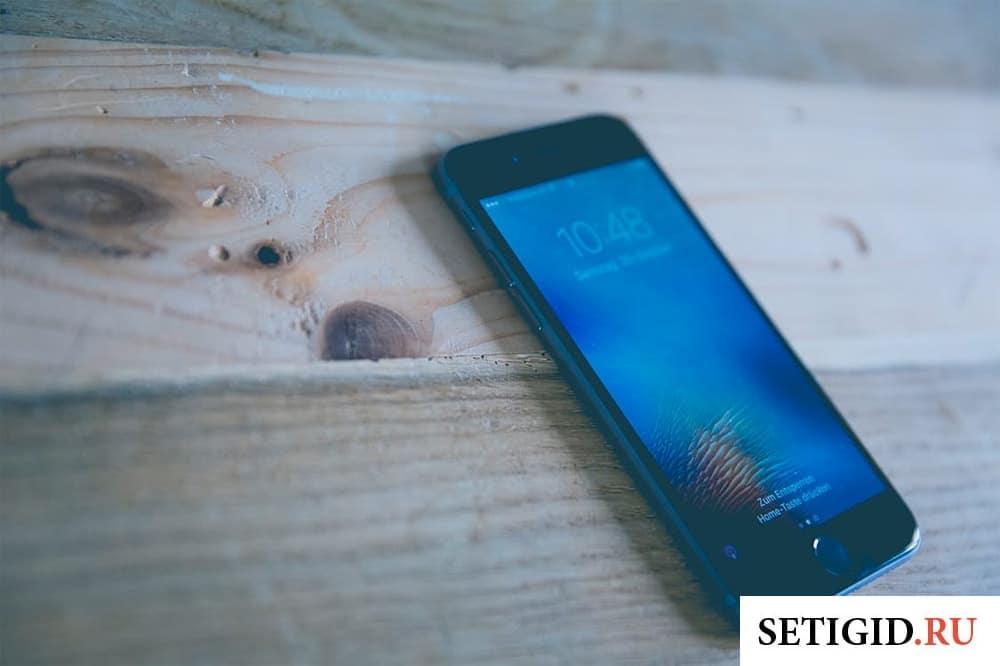 мобильный телефон лежит на деревянной поверхности