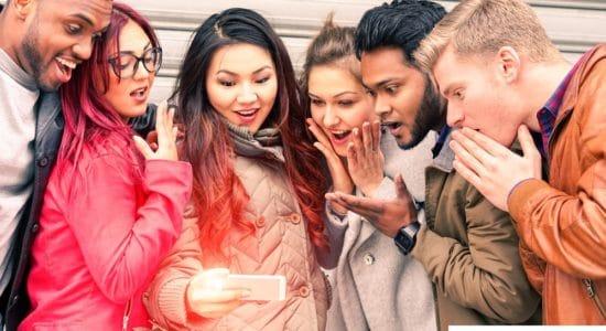 группа молодых людей смотрят на мобильный телефон