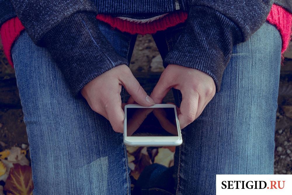 Девушка, держащая мобильный телефон