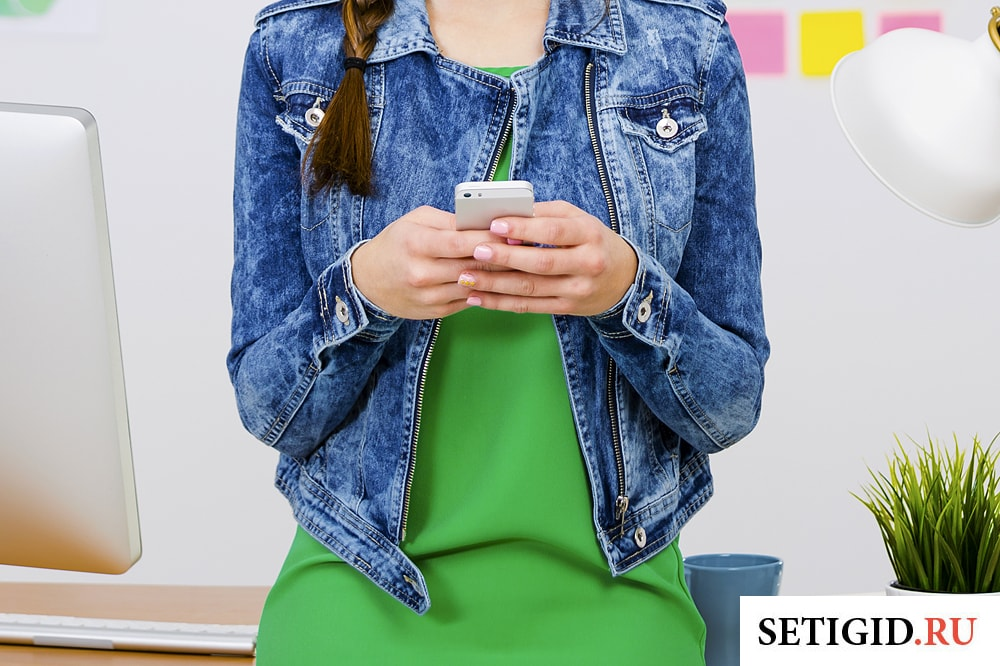 смартфон в руках у молодой девушки
