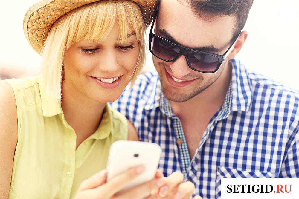 парень и девушка смотрят на экран телефона