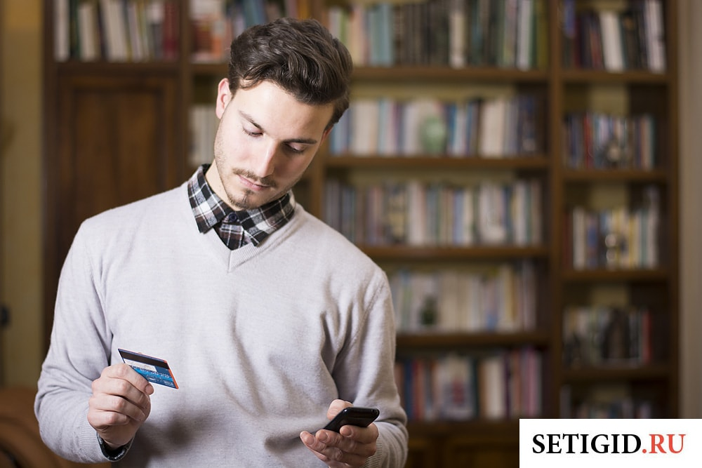 мужчина держит в руках смартфон и банковскую карту