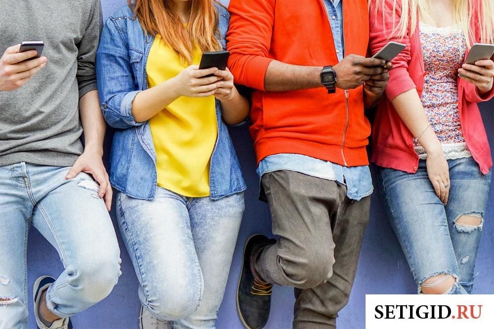 группа молодых людей с мобильными телефонами