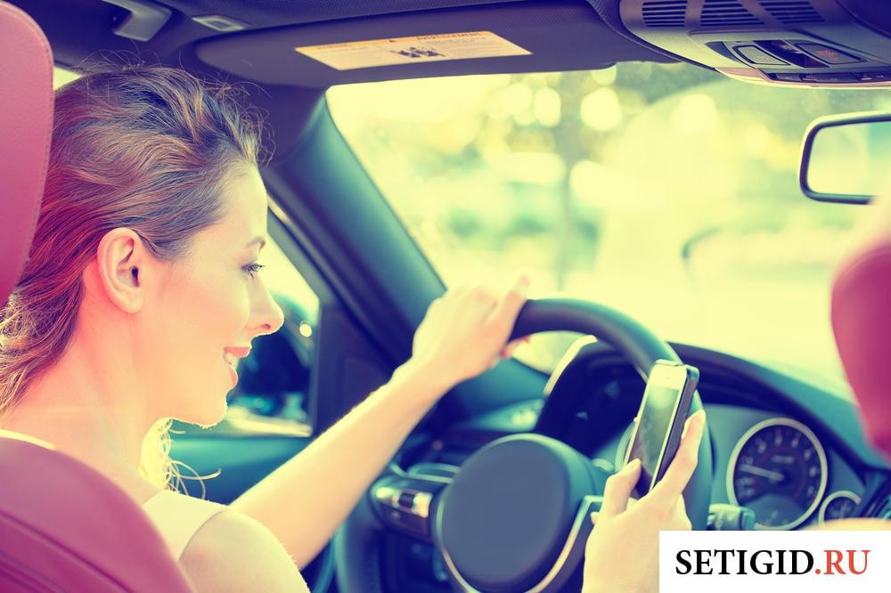 женщина водитель с мобильным телефоном