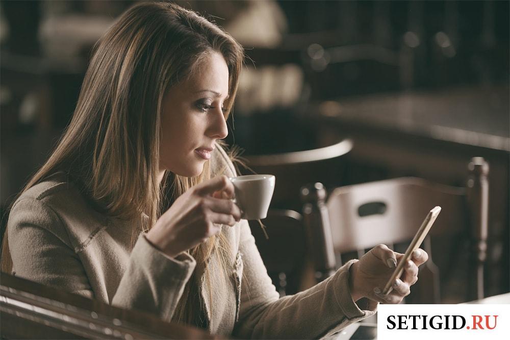 девушка пьет кофе и смотрит на экран телефона