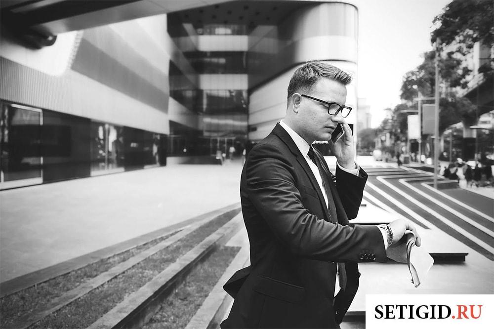 бизнесмен слушает голосовое сообщение на мобильном