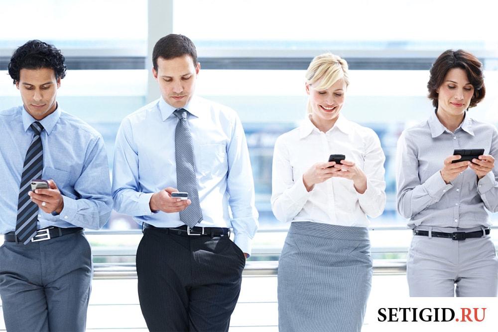 группа деловых людей смотрят в мобильные телефоны