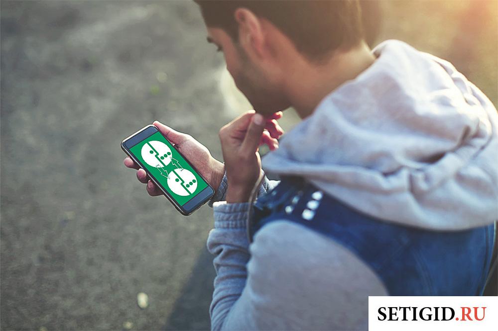 парень смотрит на экран мобильного