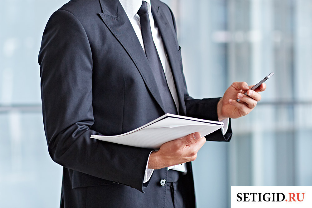 бизнесмен с документами и телефоном