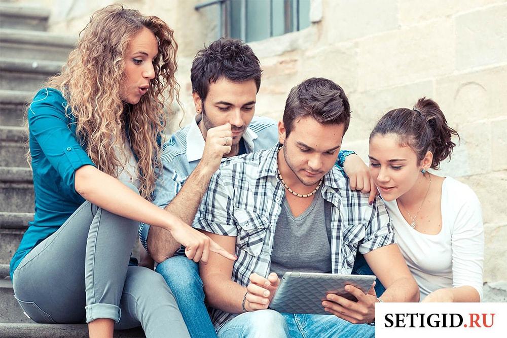 группа молодых людей смотрят на планшет