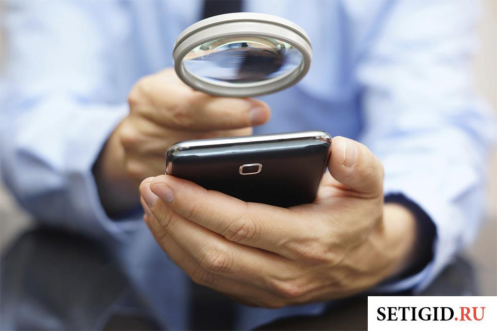 смартфон и увеличительное стекло в мужских руках