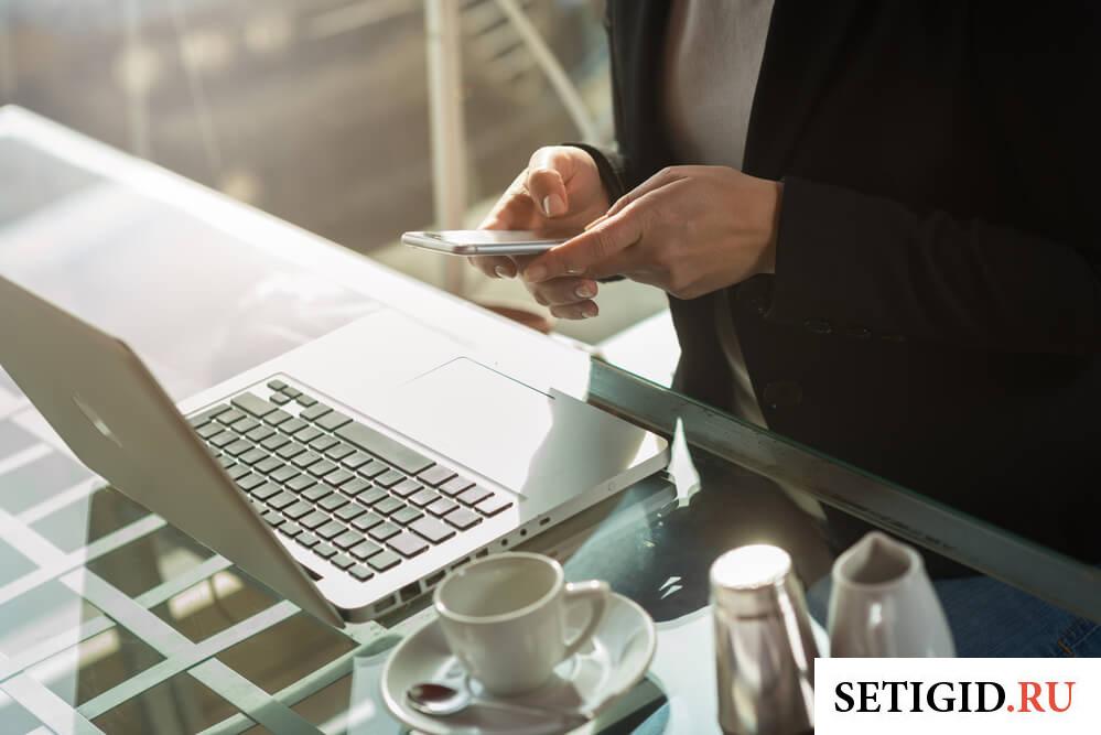 девушка сидит за столиком в кафе и смотрит на экран мобильного